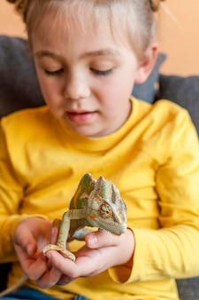 Bliska dziewczyna trzyma kameleona