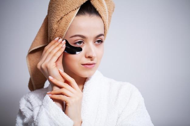 Bliska dziewczyna trzyma plastry do pielęgnacji oczu