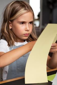 Bliska dziewczyna trzyma żółty papier