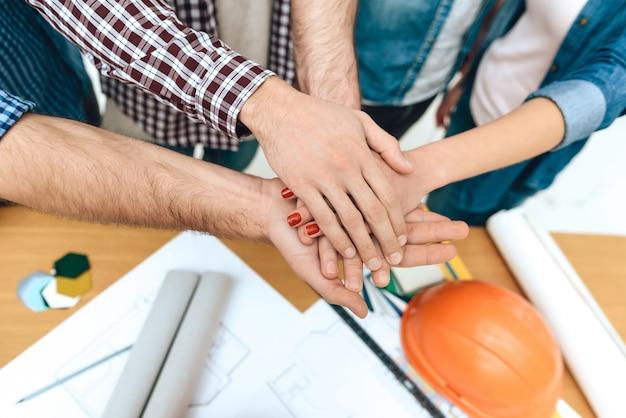 Bliska ekipa projektantów architektów trzyma się za ręce.