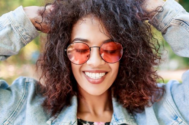 Bliska emocjonalny portret radosnej ładnej damy bawiącej się swoimi niesamowitymi kręconymi włosami.
