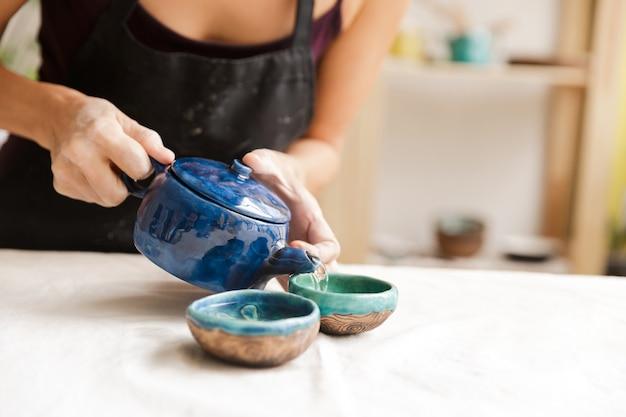 Bliska garncarza kobieta picia herbaty w warsztacie