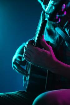 Bliska gitarzysta ręka gra na gitarze, makro. koncepcja reklamy, hobby, muzyki, festiwalu, rozrywki. osoba improwizująca inspirowana. copyspace, aby wstawić obraz lub tekst. kolorowe podświetlenie neonowe.