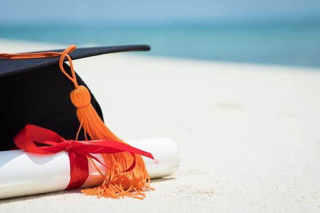 Bliska graduation cap i certyfikat na plaży
