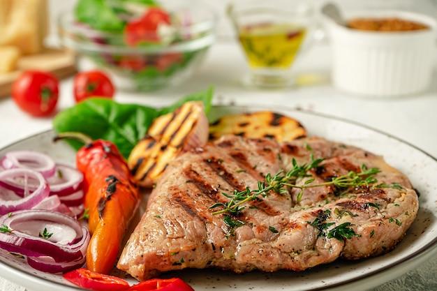 Bliska grillowany stek z ziołami, przyprawami i warzywami na talerzu