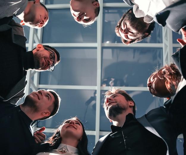 Bliska grupa szczęśliwych młodych ludzi biznesu stojących w kręgu