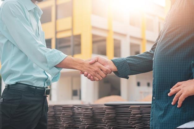 Bliska inżynier uścisnąć dłoń na budowie w koncepcji partnera osiągnięcia sukcesu w pracy zespołowej