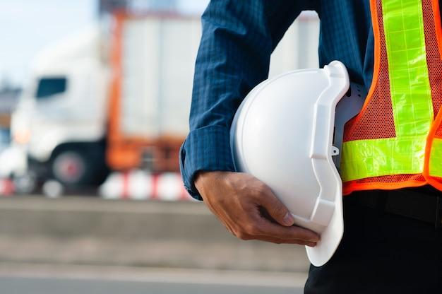 Bliska inżynieria trzymająca biały hełm kask bezpieczeństwa i tło budowy dróg