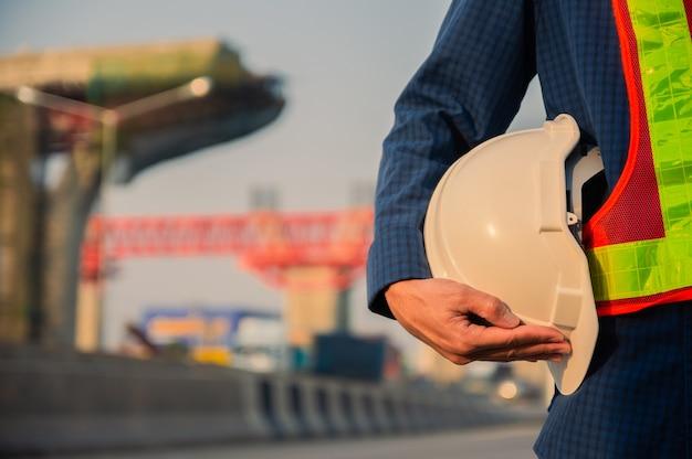 Bliska inżynieria trzymająca żółty kask kask bezpieczeństwa i tło budowy dróg