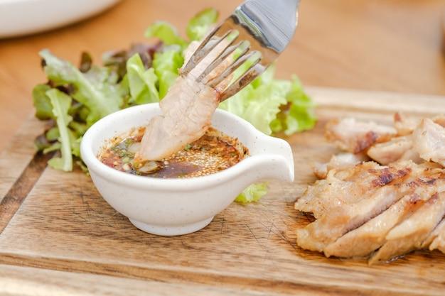 Bliska karkówka gotowana na węglu drzewnym z sosem jest ostro kwaśna. smak jest popularną przystawką w tajlandii. grillowany stek wieprzowy tajskie jedzenie
