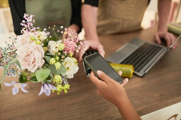 Bliska klientki płacącej w kwiaciarni za pomocą miejsca na kopię na smartfonie