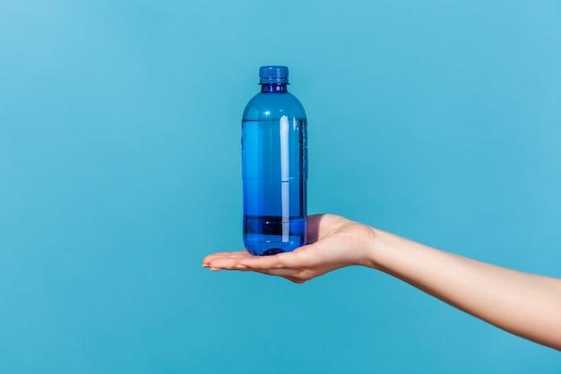 Bliska kobieca ręka demonstruje plastikową niebieską butelkę z wodą mineralną, reklama świeżego czystego napoju, najlepszy sposób na przywrócenie równowagi elektrolitów. kryty studio strzał na białym tle na niebieskim tle