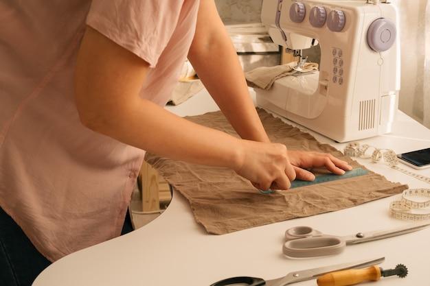 Bliska kobiece dłonie linijką, kredą i tkaniną bawełnianą, koncepcja szycia