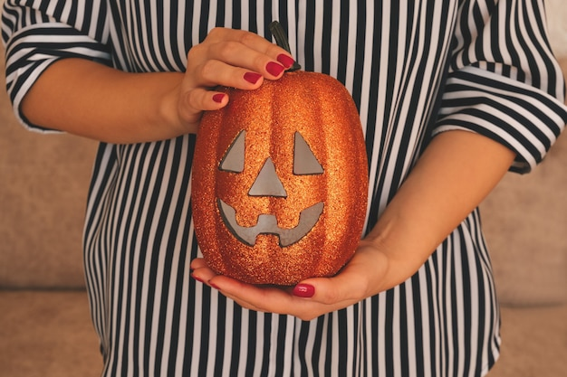 Bliska kobiece ręce trzymając dyni halloween