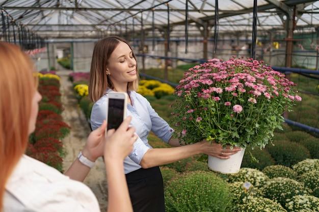Bliska kobiece ręce trzymając telefon i robienie zdjęć dziewczyny z kwiatami.