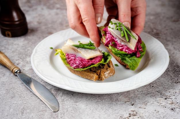 Bliska kobiecej dłoni umieścić kanapkę śledziową z burakami i zieloną sałatą na białym talerzu