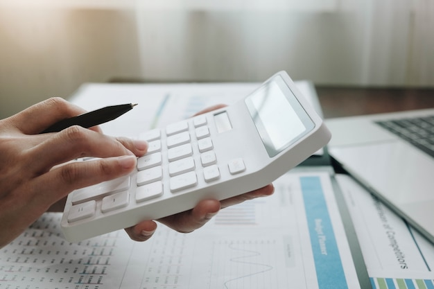 Bliska kobieta biznesu za pomocą kalkulatora i laptopa do finansów matematycznych na drewnianym biurku w pracy biurowej i biznesowej, podatki, rachunkowość, statystyki i koncepcja badań analitycznych