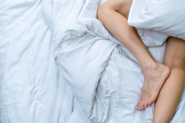 Bliska kobieta boso na łóżku nad białym kocem i prześcieradłem w sypialni domu lub hotelu. koncepcja spania i relaksu. leniwy poranek. boso kobiety leżącej.