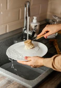 Bliska kobieta czyszczenia płyty z pędzelkiem