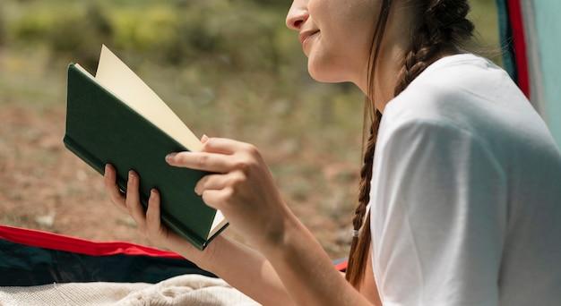 Bliska kobieta czytająca na zewnątrz