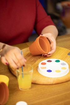 Bliska kobieta farby na glinianym garnku ceramicznym