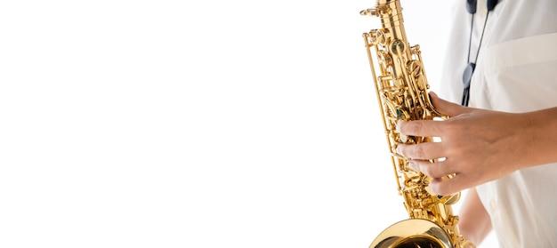 Bliska kobieta gra na saksofonie na białym tle na ścianie białego studia.