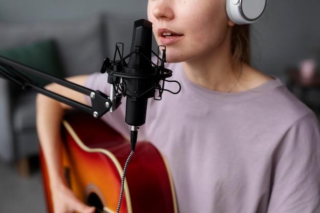 Bliska kobieta grająca na gitarze i śpiewająca