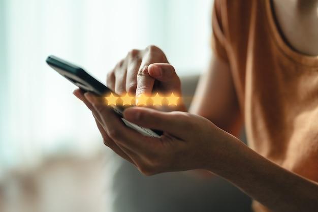 Bliska kobieta klienta dając pięć gwiazdek na smartfonie. przegląd, ocena usług, satysfakcja, doświadczenie obsługi klienta i koncepcja badania satysfakcji.