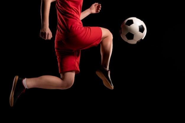 Bliska kobieta kopiąc piłkę z kolanem