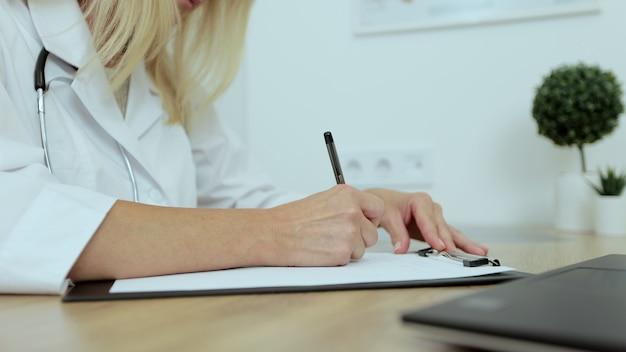 Bliska kobieta lekarz pisanie notatek w albumie rejestracyjnym, zarządzanie wizytami pacjentów w miejscu pracy. koncepcja medycyny, ludzi i chorób zakaźnych.