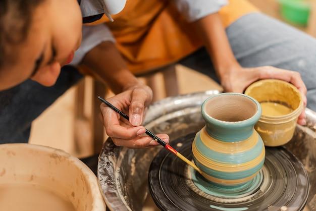 Bliska kobieta maluje gliniany garnek