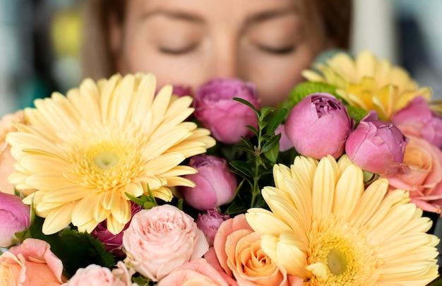 Bliska kobieta pachnąca kwiaty