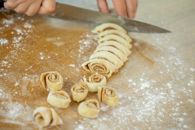 Bliska kobieta piekarz robi bułki z cukrem i cynamonem na bułeczki