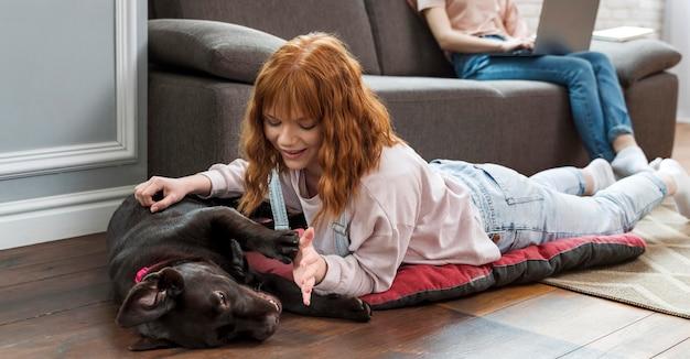 Bliska kobieta, pieszczoty psa na podłodze