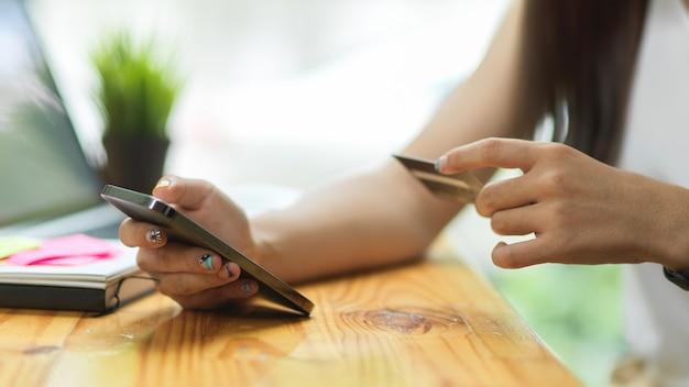 Bliska kobieta płacąca za pomocą smartfona kartą kredytową, płatności bezgotówkowe, koncepcja płatności online