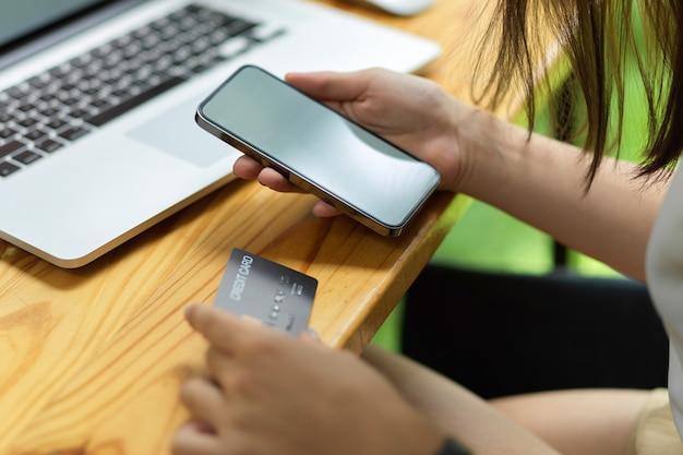 Bliska kobieta przesyła pieniądze za pośrednictwem smartfona i telefonu komórkowego z kartą kredytową z pustym pustym ekranem