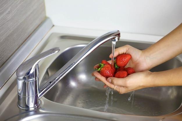 Bliska kobieta ręce do mycia owoców