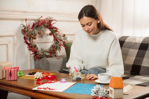 Bliska kobieta robi kartkę z życzeniami na nowy rok i boże narodzenie 2021 dla przyjaciół lub rodziny, rezerwacja złomu, majsterkowanie. pisząc list z najlepszymi życzeniami, zaprojektuj jej własną kartkę. święta, uroczystości.