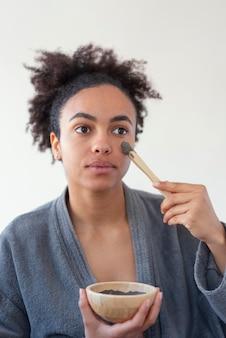 Bliska kobieta stosując zabieg na twarz