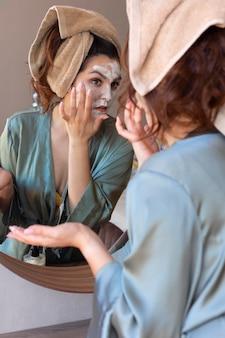 Bliska kobieta stosująca krem do twarzy