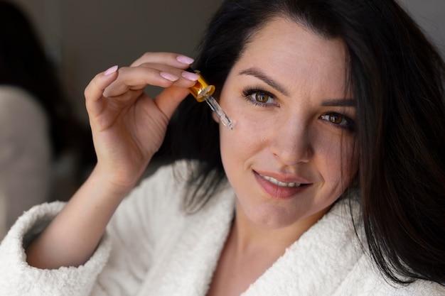 Bliska kobieta stosująca serum do twarzy