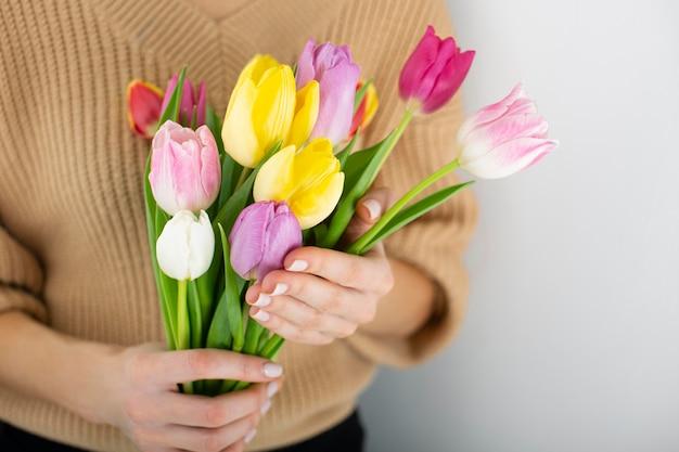 Bliska kobieta trzyma bukiet tulipanów