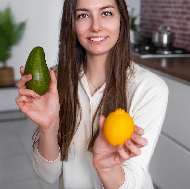 Bliska kobieta trzyma cytrynę i awokado