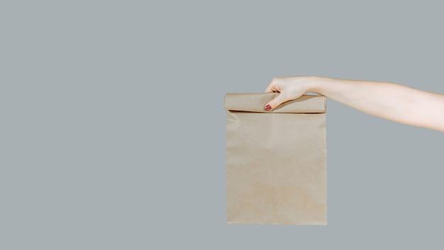 Bliska kobieta trzyma w ręku brązowy jasny pusty pusty papier rzemieślniczy worek na wynos