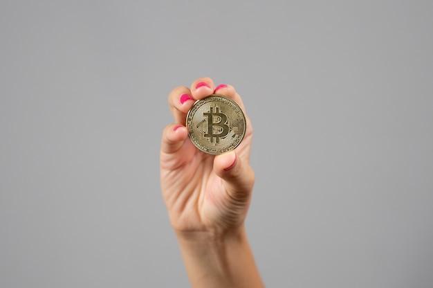 Bliska kobieta trzyma w ręku złoty bitcoin na szarym tle. koncepcja waluty kryptograficznej.