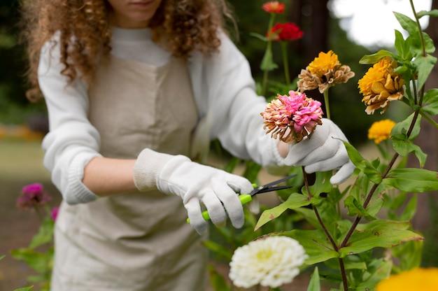 Bliska kobieta trzymająca rękawiczki do podlewania