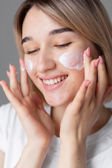 Bliska kobieta używa kremu do twarzy