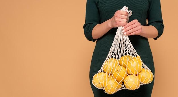 Bliska kobieta w ubranie przewożących torbę wielokrotnego użytku żółwia