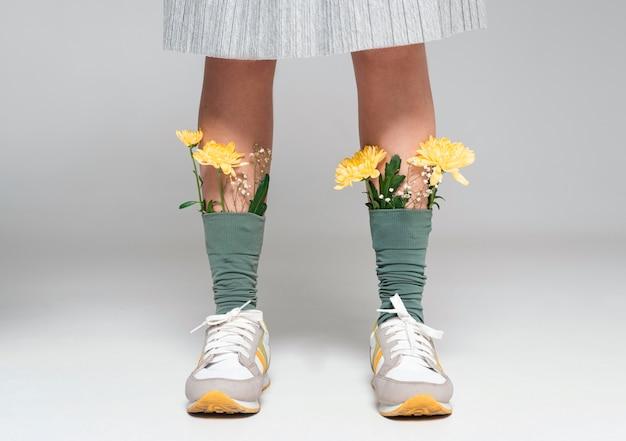 Bliska kobieta z kwiatami na skarpetkach