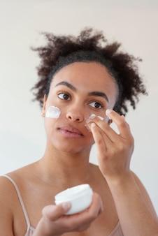Bliska kobieta za pomocą kremu do twarzy